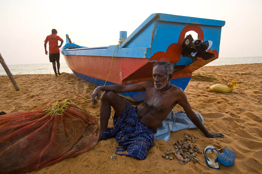Elderly fishermen resting after counting his catch of shells, Kochuveli, Kerala