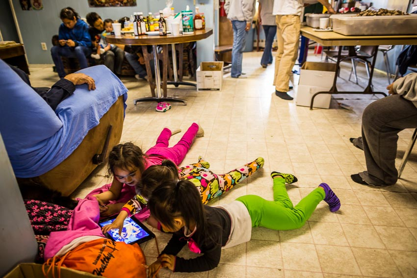 Children play with an iPad at the feast celebrating Kaktovik's first whale of the year.