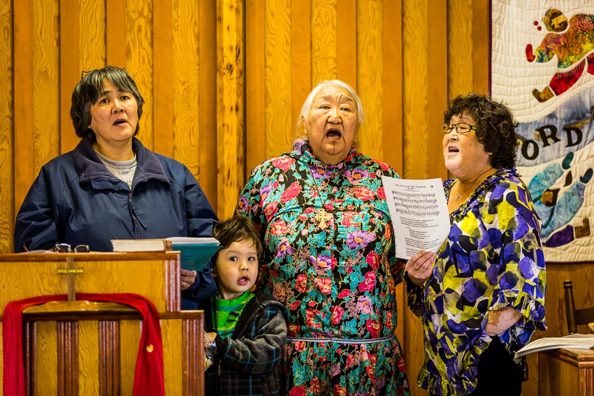 Rev. Mary Ann Warden, second from right, leads her congregation in worship at the Kaktovik Presbyterian Church. They sing in both English and Inupiaq.